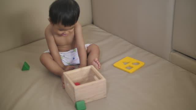 stockvideo's en b-roll-footage met slo mo aziatische babyjongen spelen houten speelgoed - one baby boy only