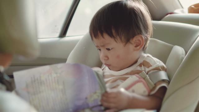 asian baby boy reading book traveling by car. - road trip stock videos & royalty-free footage