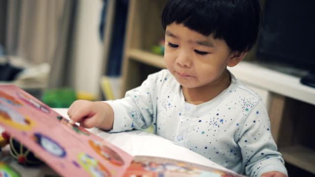 vídeos de stock e filmes b-roll de asian baby boy reading book - bebés meninos