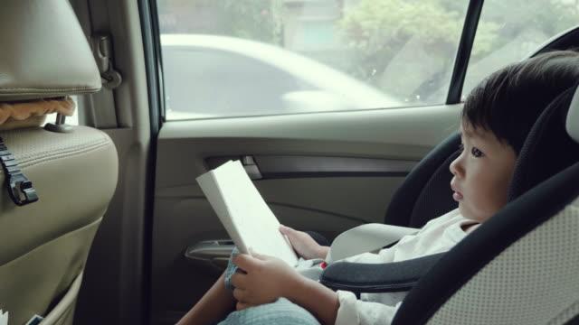vídeos de stock, filmes e b-roll de menino asiático no assento do carro. - cadeirinha cadeira