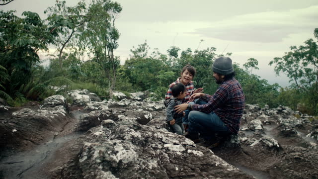 asian baby boy sitting on timber with his family in forest. - young family stock videos and b-roll footage