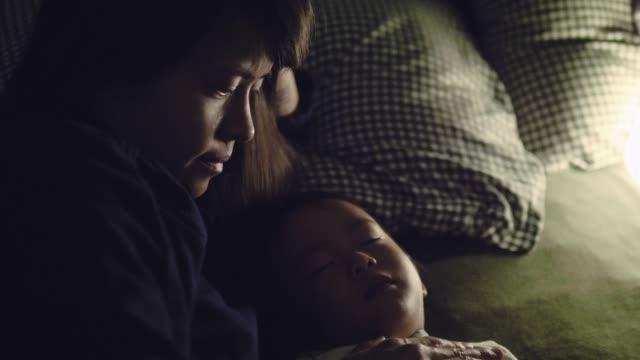 asiatisk pojke sova inomhus på säng med mor hemma. - människofinger bildbanksvideor och videomaterial från bakom kulisserna