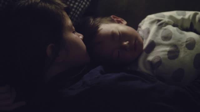 自宅で母親とベッドで屋内で眠るアジア男の子。 - 寝室点の映像素材/bロール