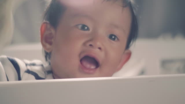 Asian baby boy standing in crib and laughing