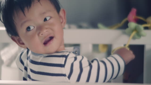 asian baby boy standing in crib and looking at mother - cot stock videos & royalty-free footage