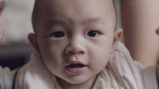 asian baby boy taking first steps with the support of his mother - steps stock videos & royalty-free footage