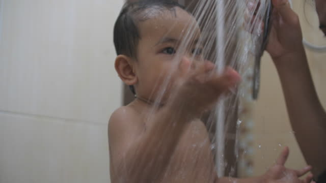 slo mo asian baby boy taking shower - vasca da bagno video stock e b–roll