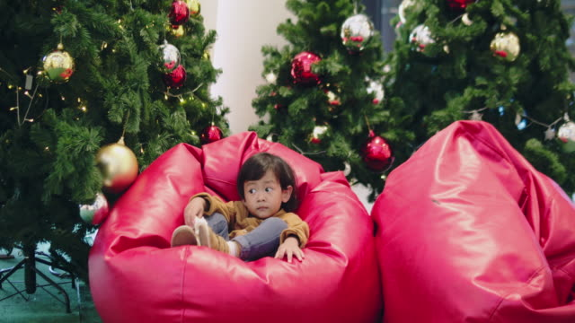 asian baby boy touching a ball on the christmas tree in the new year - - bean bag stock videos & royalty-free footage