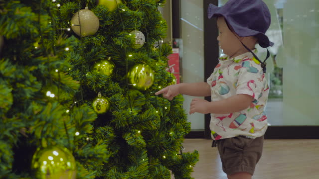 asian baby boy touching a ball on the christmas tree in the new year - decorating the christmas tree stock videos & royalty-free footage