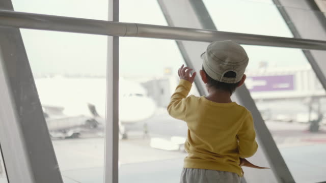asian baby boy watching planes at the airport - arrival departure board stock videos & royalty-free footage