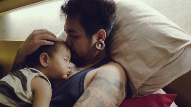 Asian Baby Boys Sleeping With Father In Bedroom.