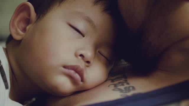stockvideo's en b-roll-footage met aziatische baby jongens slapen met vader in slaapkamer. - een dutje doen