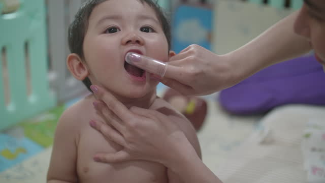 asian baby cleaned tongue with soft rubber brush by his mother - human tongue stock videos & royalty-free footage