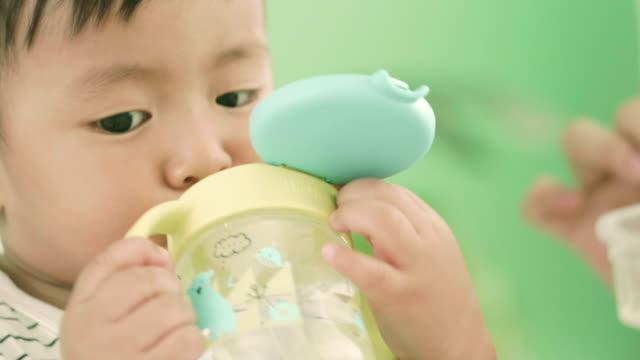 アジアの赤ちゃんの飲料水 - 粉ミルク点の映像素材/bロール