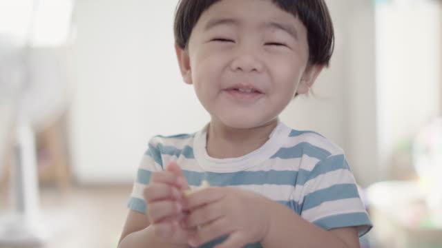 vidéos et rushes de bébé asiatique, manger et s'amuser dans la chambre à coucher - genderblend