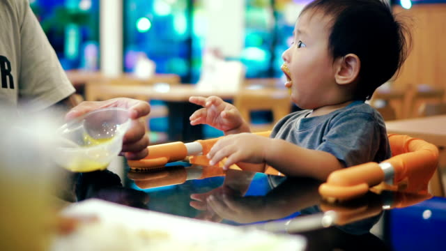 asian baby (6-11 months) eating baby food in restaurant. - feeding stock videos & royalty-free footage