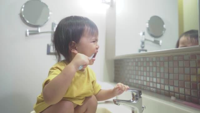 vídeos y material grabado en eventos de stock de asiática niña cepillando los dientes en el baño - cuidado del cuerpo