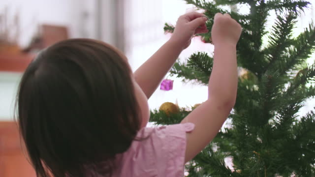 vídeos de stock, filmes e b-roll de menina asiática, decorar a árvore de natal com enfeites - enfeitar a árvore de natal