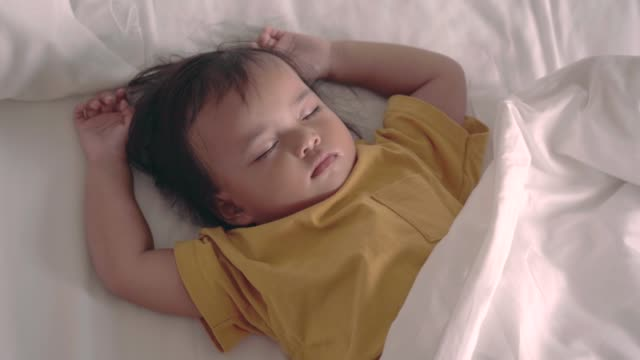 asian baby girl deeply sleeping on the comfortable white bed - babies only stock videos & royalty-free footage