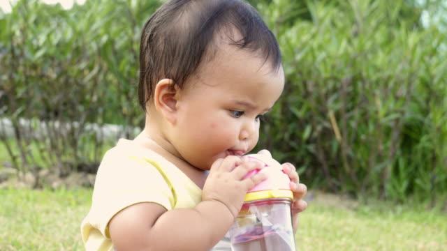 vidéos et rushes de bébé asiatique buvant l'eau dans le jardin. une fille s'asseyant à l'extérieur. - tout petit