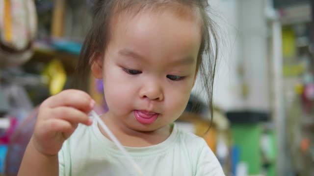 asiatisk flicka äter mjölk hemma. - endast en flickbaby bildbanksvideor och videomaterial från bakom kulisserna