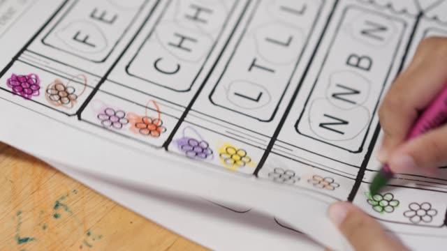 asian baby girl elementary school age doing english homework. - disegnare video stock e b–roll