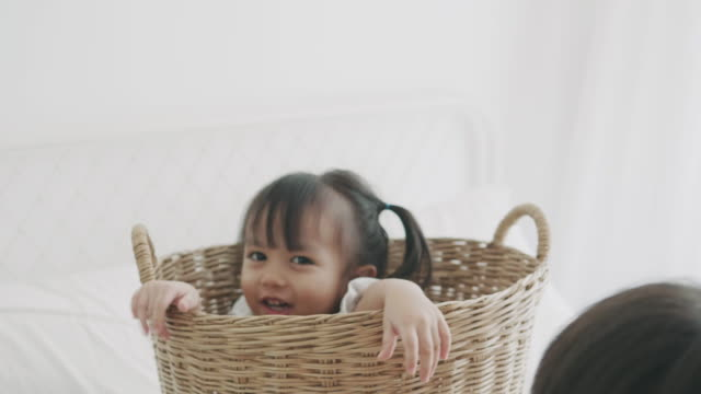 asian baby girl hiding in the basket while her brother want to play together - peekaboo game stock videos & royalty-free footage