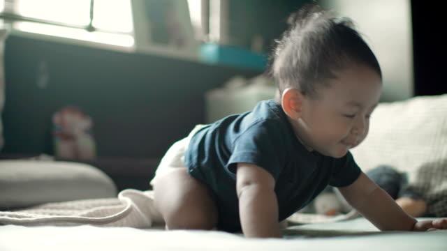アジアの女の子は、ベッドの部屋のベッドにクロールされます。タイ - 這う点の映像素材/bロール