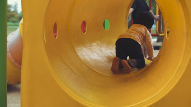 asian baby girl is enjoying to climb and play equipment at the playground - playground stock videos & royalty-free footage