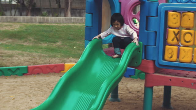 Asian baby girl is enjoying to climb and play equipment at the playground