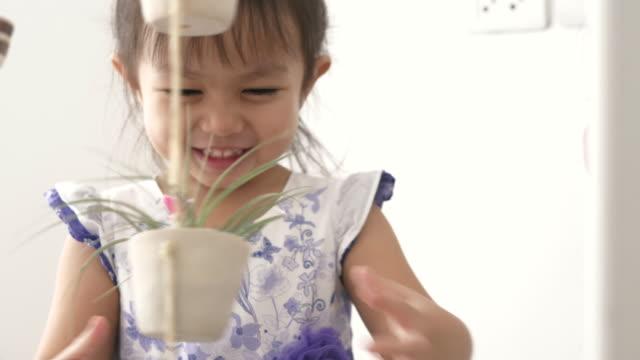 Aziatische meisje is het zetten van kleine violet cactus boom aan bloempot opknoping met haar moeder