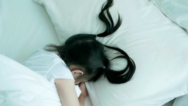 asian baby girl is sleeping and her brother hiding in the blanket on the bed - pigtails stock videos & royalty-free footage