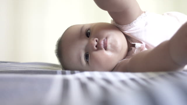 asian baby girl lying and rolling over on bed - roll over stock videos and b-roll footage
