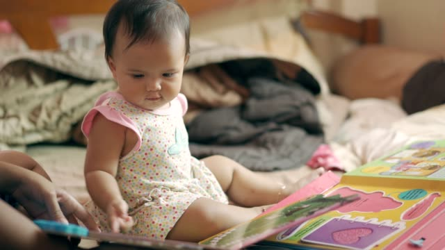 asian baby girl playing and reading playbook or activity book with mother - toddler stock videos & royalty-free footage