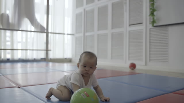 asian baby girl playing on wooden floor at home - 手を伸ばす点の映像素材/bロール