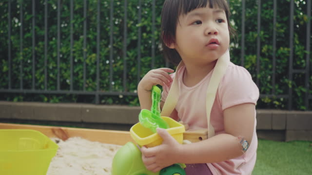 vídeos y material grabado en eventos de stock de asiática niña jugando al aire libre en el arenero en el patio trasero - 2 kid in a sandbox