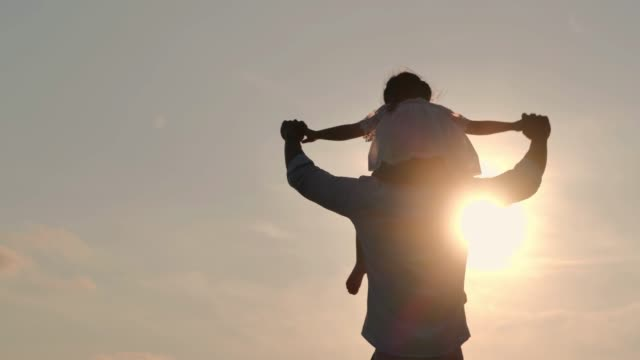 asian baby girl ride the neck of father.dad and baby girl playing together outdoors on a summer.happy family watching the sunset on the beach.holiday travel concept.vacations - istock - weekend activities stock videos & royalty-free footage