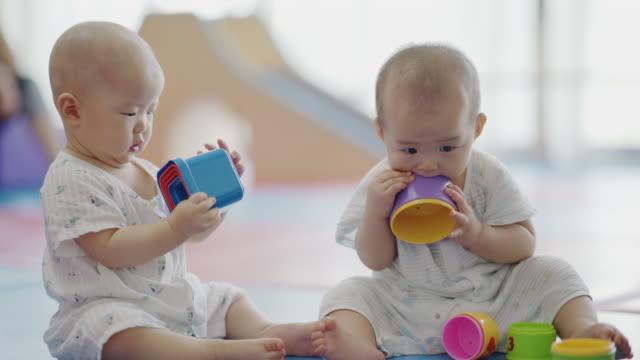 asian baby girl sitting on floor playing cheerfully / chongqing, china - 遊具点の映像素材/bロール