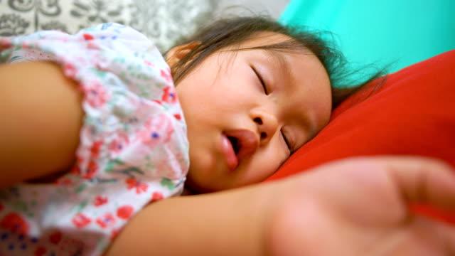 asiatisches babymädchen schläft auf dem bett. - schlafenszeit stock-videos und b-roll-filmmaterial