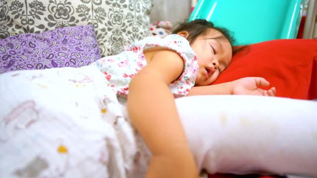 vidéos et rushes de petite asiatique fille de dormir sur le lit. - yeux fermés