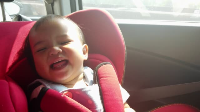 asian baby girl smiling and laughing on her car safety seat during during parent drive - belt stock videos & royalty-free footage