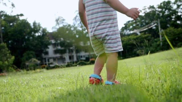 vidéos et rushes de train asiatique de fille de bébé pour marcher et s'asseoir sur l'herbe verte et jouer, concept de jour de mère, images de mouvement lent. - pelouse