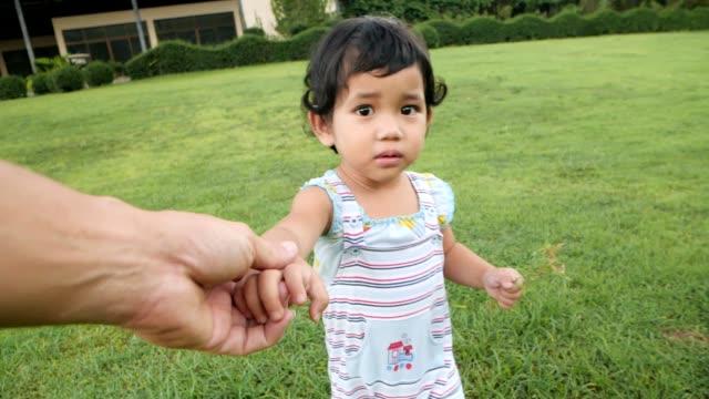 vídeos de stock, filmes e b-roll de trem asiático do bebé para andar e sentar-se na grama verde e no jogo, conceito do dia de mãe, metragem do movimento lento. - bebês meninas