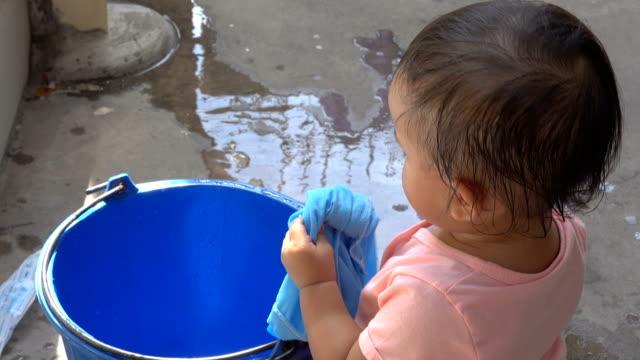 vidéos et rushes de bébé asiatique lavant une chemise bleue à la maison. le plancher en béton se mouillant des vêtements de lavage de bébé. - lessive corvée domestique