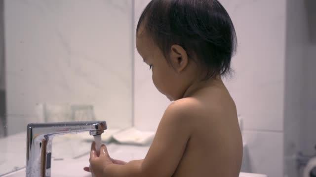 asiatiskapojke flicka tvätta händerna på sink - endast en flickbaby bildbanksvideor och videomaterial från bakom kulisserna
