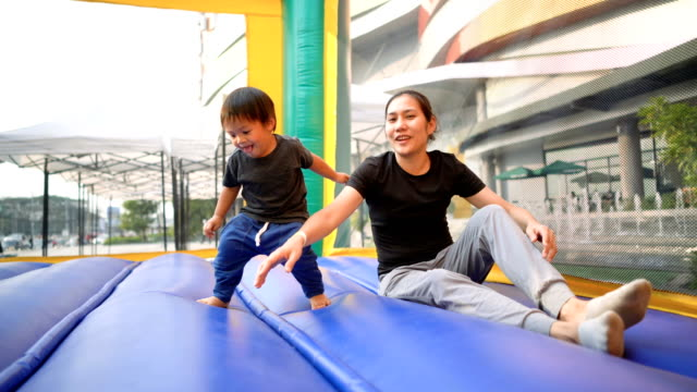 asian baby jumping in inflatable playground with mother. - sports equipment stock videos & royalty-free footage