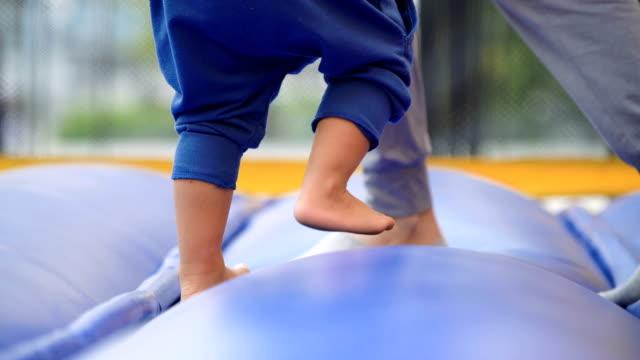 Aziatische baby springen in opblaasbare speeltuin met moeder.