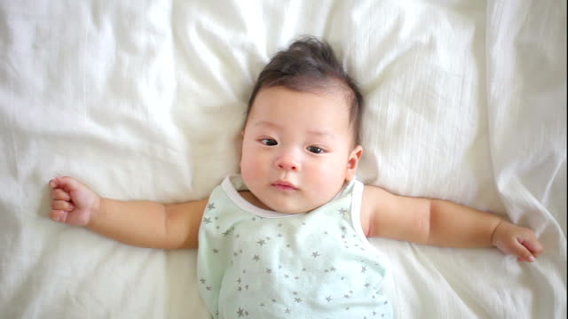 asian baby laydown on white bed