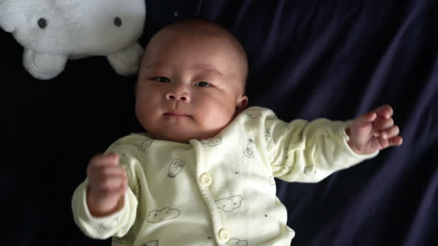 asian baby lying on bed and looking at camera - babies only stock videos & royalty-free footage
