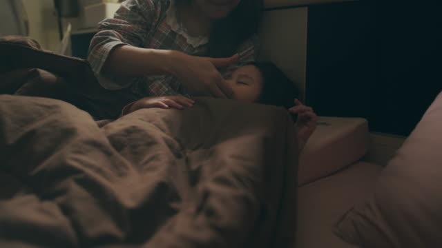 夜に寝室で彼女の母親と一緒に寝ているアジアの赤ちゃんや子供の女の子。彼女は一日中遊ぶのに疲れた - ベッド点の映像素材/bロール